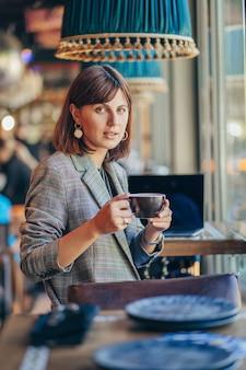 Bella ragazza in giacca grigia, bere caffè e lavorare su net-book nella caffetteria. libero professionista che lavora in una caffetteria. imparare in linea.