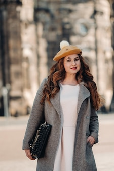 Una bella ragazza con un cappello sta con una macchina da scrivere nella città vecchia di dresda