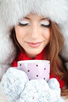Bella ragazza in cappello con il primo piano della tazza