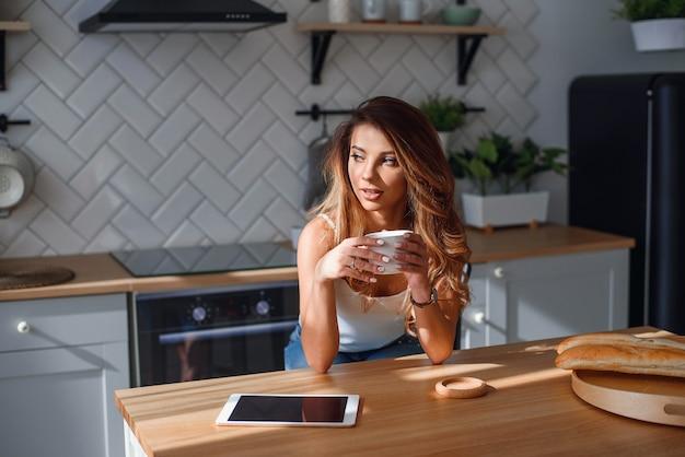 Bella ragazza che si rilassa e che beve caffè sulla cucina moderna alla moda al mattino.