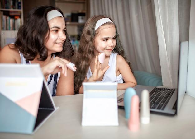 Bella ragazza e sua madre guardando la master class di bellezza con compresse online e facendo la procedura termale da soli, mamma e figlia si divertono con la maschera liscia sul viso, salone di bellezza a casa