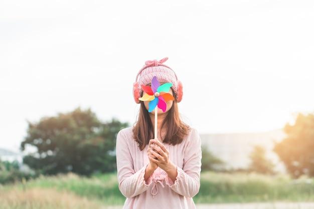Bella ragazza che tiene il giocattolo del vento o generatore eolico o girandola e cappello di lana