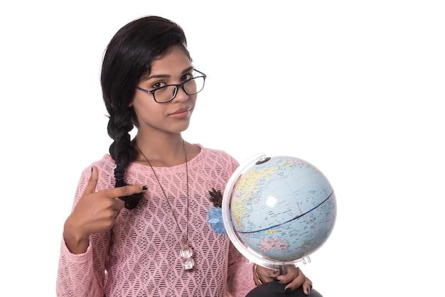 Bella ragazza in possesso di un globo del mondo isolato su uno sfondo bianco