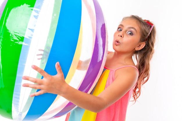 Una bella ragazza tiene una grande palla gonfiabile color ferita ed è agitata