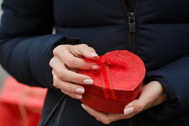 La bella ragazza tiene una scatola con un regalo nelle sue mani. il concetto per san valentino