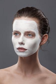 Bella ragazza viene applicata una maschera cosmetica bianca da punti neri. isolato,