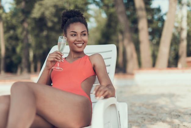 Bella ragazza sta bevendo champagne da vetro e sorridente