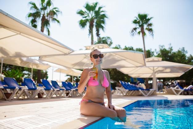 La bella ragazza sta bevendo un cocktail in piscina.