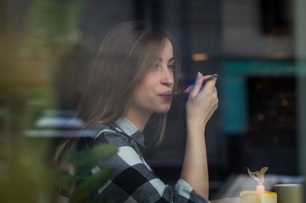 La bella ragazza sta bevendo il tè in un caffè