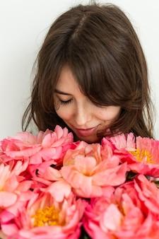 La bella ragazza è felice con i fiori per il suo compleanno, il viso di una ragazza da vicino con le peonie, il giorno di san valentino