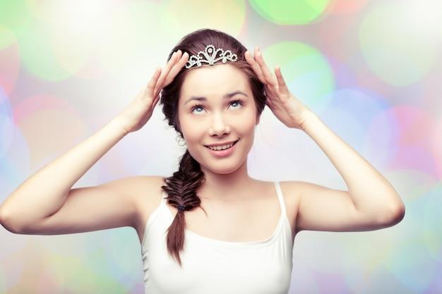 La bella ragazza sta mettendo su un diadema di diamanti e lo sta ammirando