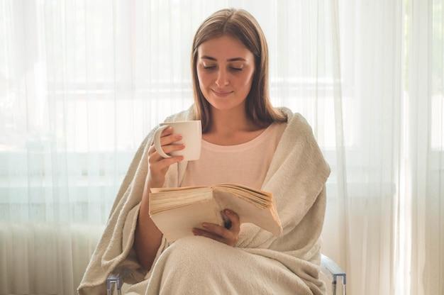 La bella ragazza sta leggendo un libro con una tazza di tè caldo