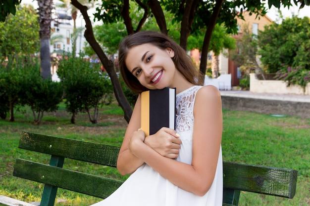 La bella ragazza è seduta sulla panchina nel parco e abbraccia un libro