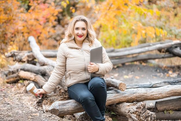 Una bella ragazza è seduta sui tronchi in un parco autunnale con in mano laptop e tazze di caffè