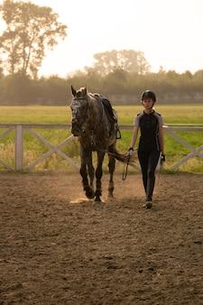 Bella ragazza fantino in piedi accanto al suo cavallo che indossa un'uniforme speciale su uno sfondo di cielo e campo verde su un tramonto