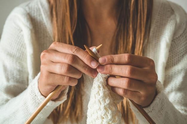 Bella ragazza lavora a maglia un maglione caldo sul letto. lavorare a maglia come hobby. accessori per maglieria.