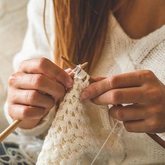 La bella ragazza lavora a maglia un maglione caldo