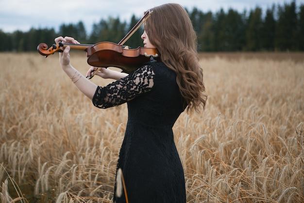 Una bella ragazza in un abito di pizzo suona il violino in un campo di grano