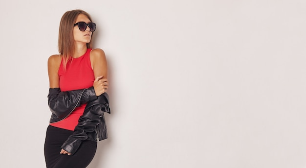 Bella ragazza in una giacca di pelle e una maglietta rossa.