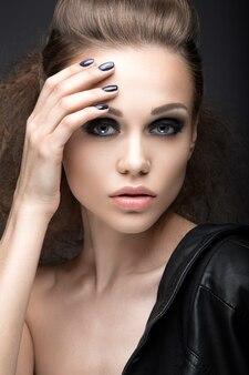Bella ragazza in giacca di pelle con trucco luminoso e manicure cat's eye.