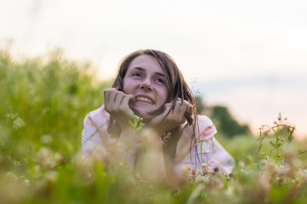 Una bella ragazza giace nell'erba e nei fiori di campo tenendo la testa sulle mani e sorride.