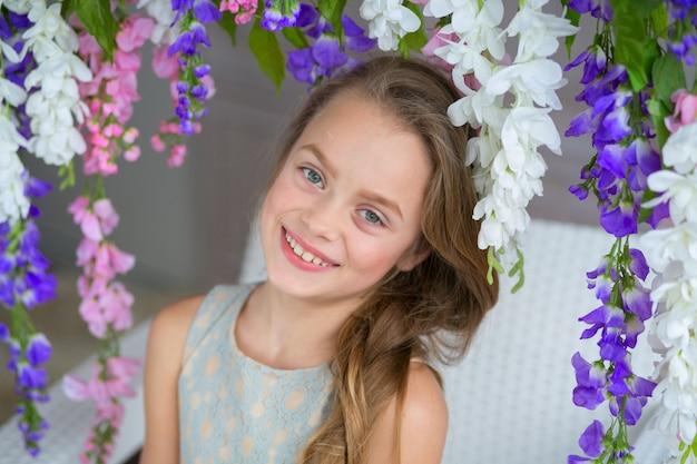Bella ragazza in un abito leggero in posa con arbusti da fiore.