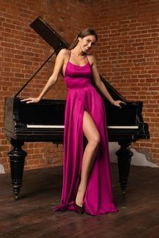 Bella ragazza in abito rosso classico lungo in posa con il vecchio pianoforte. - immagine