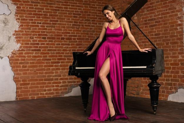 Bella ragazza in abito rosso classico lungo in posa con il vecchio pianoforte