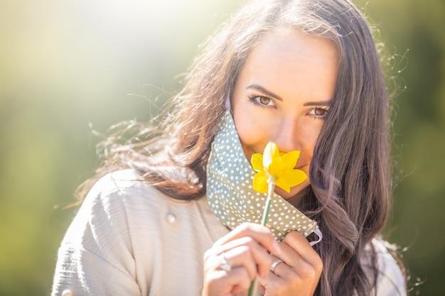 La bella ragazza guarda la telecamera annusando un fiore, indossando solo metà della sua maschera facciale a pois.