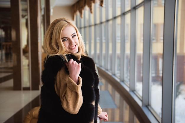 Bella ragazza guarda attraverso la finestra del business center