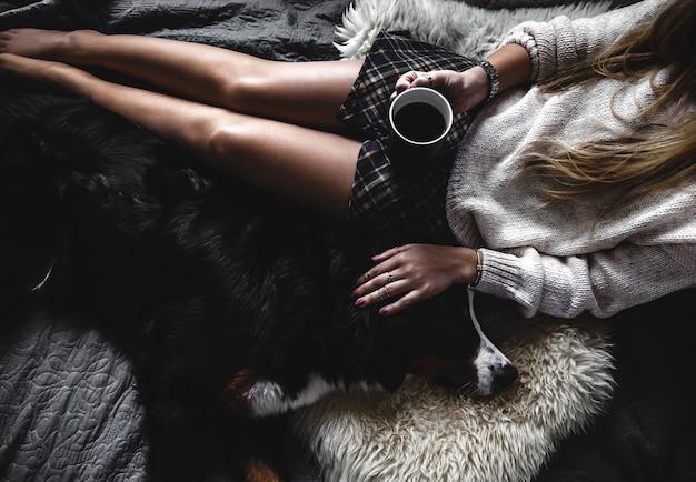 Bella ragazza sdraiata e il suo simpatico cane bovaro del bernese sul letto, elegante, alla moda, accogliente
