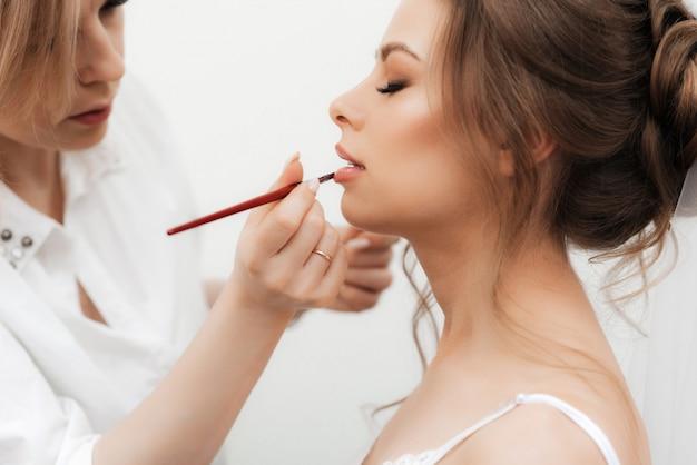 Bella ragazza makeup artist fa il trucco e dipinge le labbra in un salone di bellezza professionale