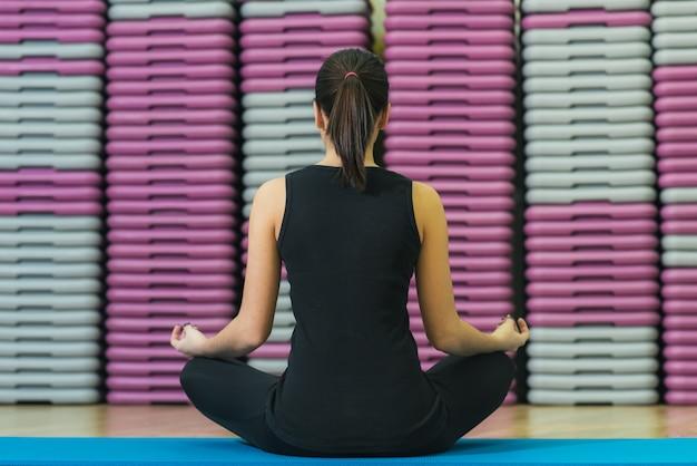 Bella ragazza sulla stuoia che fa yoga, vista posteriore
