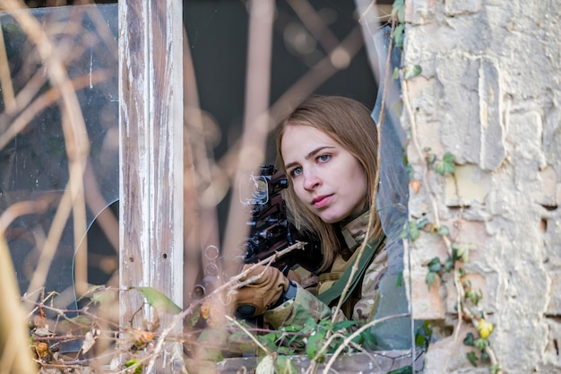 Bella ragazza in uniforme militare con una pistola softair in un edificio abbandonato guardando fuori dalla finestra