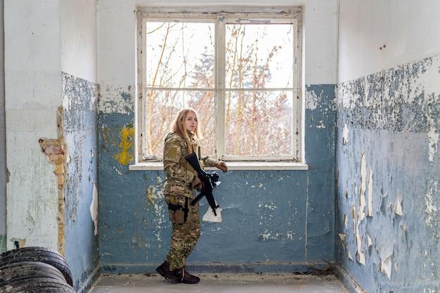 Bella ragazza in uniforme militare con una pistola softair in un edificio abbandonato