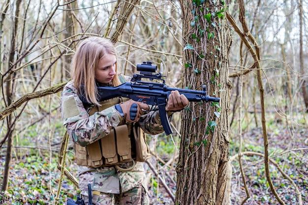 Bella ragazza in uniforme militare con una pistola airsoft nella foresta
