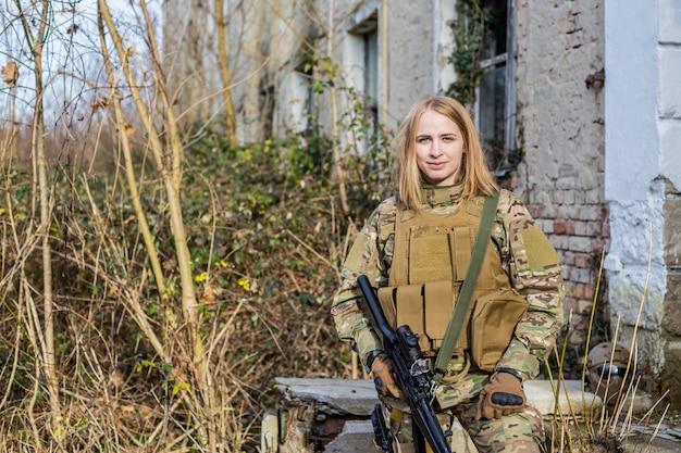 Bella ragazza in uniforme militare con una pistola di airsoft davanti a un edificio abbandonato