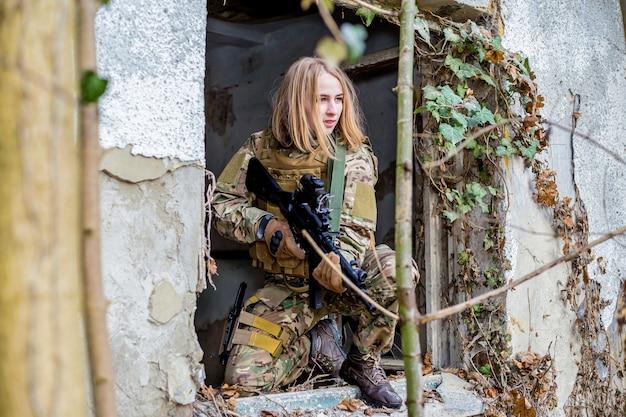 Bella ragazza in uniforme militare con una pistola di airsoft che si siede su una finestra di un edificio abbandonato