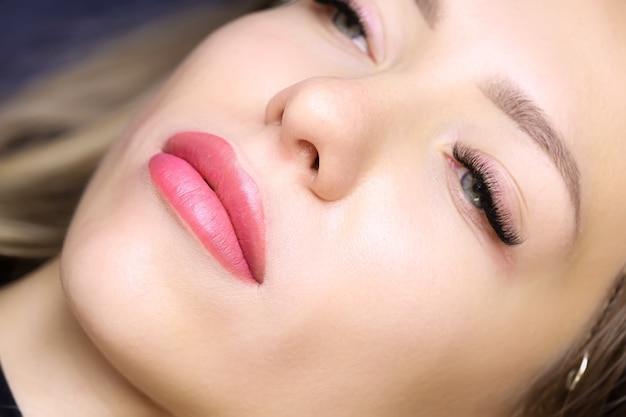 Modello di bella ragazza dopo la procedura di trucco permanente delle labbra