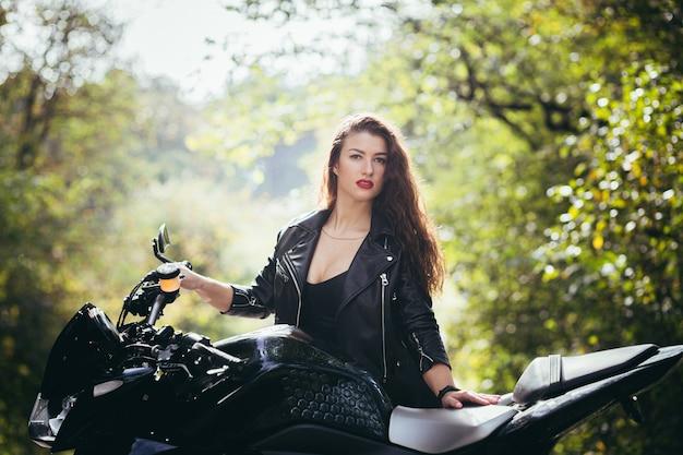Bella ragazza vicino alla moto nera, ritratto, nel bosco vicino alla strada, autunno