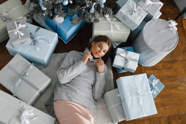 Bella ragazza vicino all'albero di natale è circondata da regali, vista dall'alto. la ragazza si rallegra ai regali