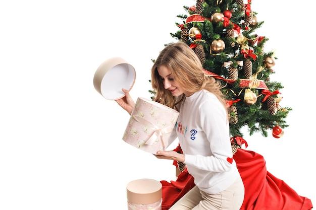 La bella ragazza vicino all'albero apre un regalo