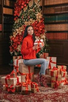 Una bella ragazza con un maglione di capodanno, sdraiata su una montagna di regali.