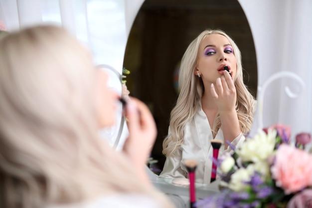 Una bella ragazza dipinge le labbra davanti a uno specchio.
