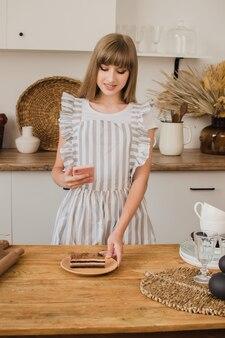 Il pasticcere o la casalinga della bella ragazza fa una foto del dessert sul telefono