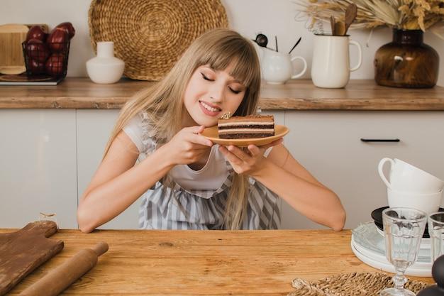 Una bella ragazza pasticciera o casalinga si siede in cucina con il dessert e guarda pensierosa