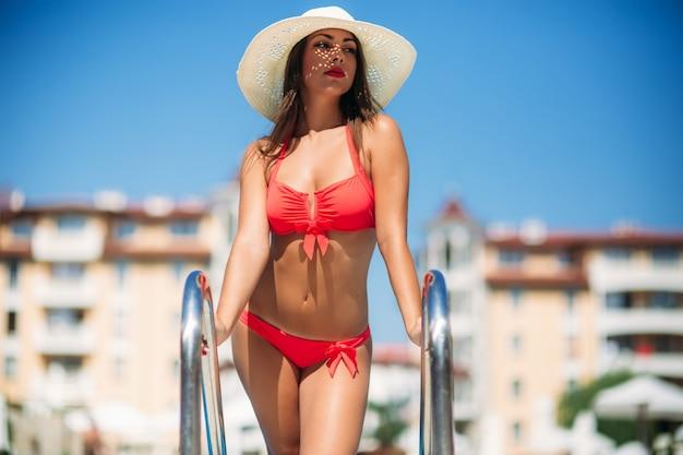 Una bella ragazza in costume da bagno rosa che prende il sole a bordo piscina.