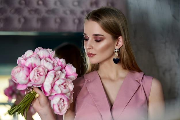 La bella ragazza in una tuta rosa che tiene i fiori alla finestra