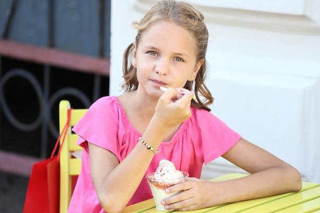 Una bella ragazza con una maglietta rosa si siede a un tavolo giallo e mangia il gelato