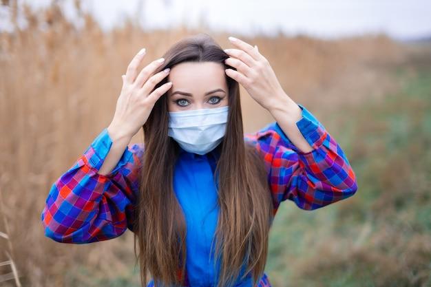 Bella ragazza in un abito scozzese con una mascherina medica in un campo di canne